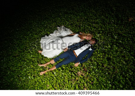 groom and bride laying in the grass at night - stock photo