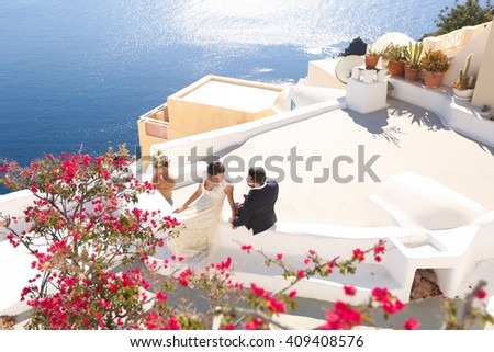 groom and bride on the roof of a house in Santorini