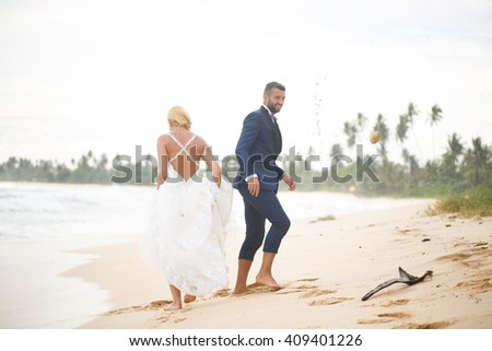 groom and bride playing on the beach on a tropical island