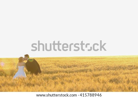 groom and bride posing in the field - stock photo