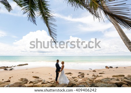 groom and bride posing on the beach on a tropical island - stock photo
