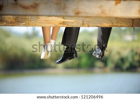 groom and bride sitting on bridge - stock photo