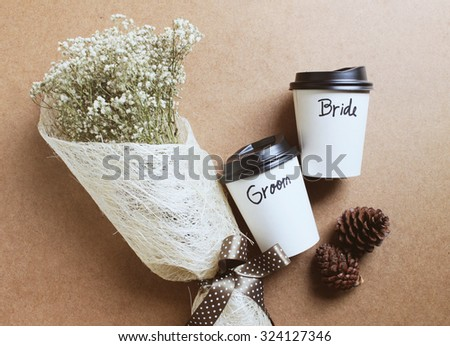 Groom and bride written on coffee cup with bouquet of flower for wedding concept - stock photo