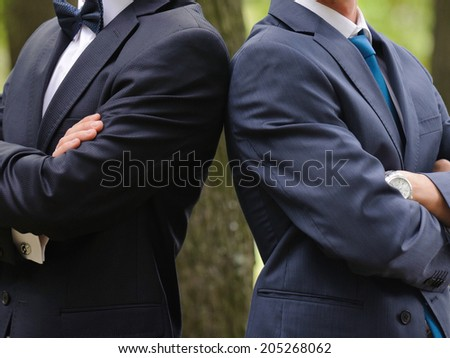 groom and groomsman standing shoulder to shoulder - stock photo