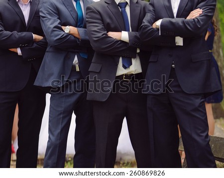 groom and groomsmen standing with crossed hands - stock photo