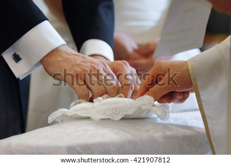 Groom and priest hands taking wedding ring