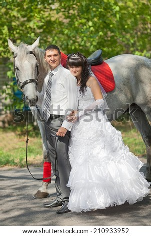 groom and the bride during walk in their wedding day against a grey horse - stock photo