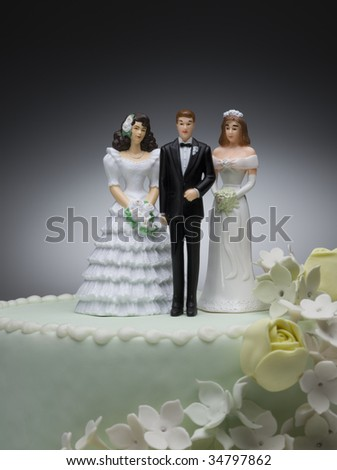 Groom and two bride figurines on top of wedding cake - stock photo
