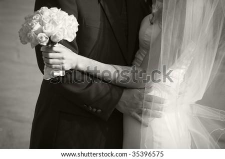 Groom arm embracing his bride. - stock photo