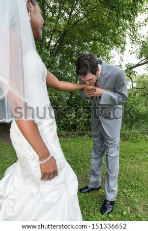 Groom bending down kissing bride's hand during wedding day - stock photo