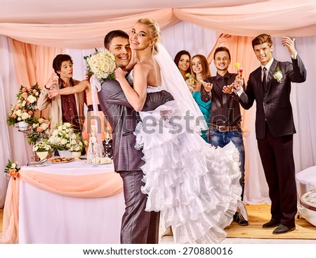 Groom  carries bride on his hands  at wedding. Guests clap. - stock photo