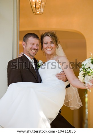 Groom Carrying Bride into Home - stock photo