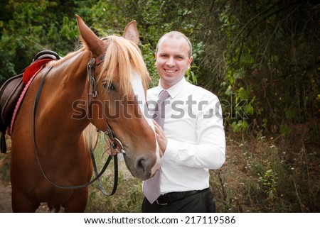 groom  during walk in their wedding day against a brown horse - stock photo