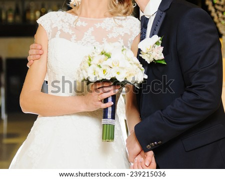 groom embracing bride with white wedding bouquet