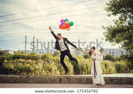 Groom flies on the balloons, but the bride holds his hand. Funny wedding. Groom jumps and flies on balloons. Young husband flying from his wife. Funny wedding concept. Happy Valentines day! - stock photo
