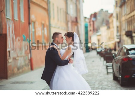 Groom gentle tilted bride, holding her in his arms and passionately kisses, wedding photo on a sunny day on a background of sand-colored walls. Newly married couple dancing in park, street tango. - stock photo