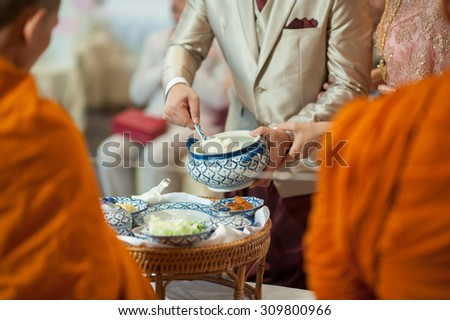 Groom give alms food to a Buddhist monk in traditional thai wedding ceremony - stock photo