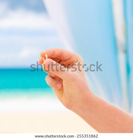 Groom giving an engagement ring to his bride. Wedding ceremony on a tropical beach in blue. Wedding and honeymoon concept. - stock photo