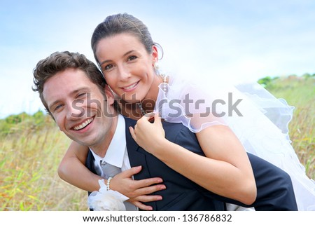 Groom giving pigguback ride to bride - stock photo