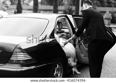 Groom helps bride to go out of the black Mercedes