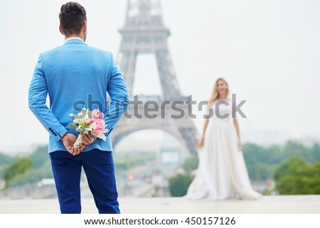 Groom hiding the wedding bouquet behind his back and going to offer it to a bride. Romantic wedding couple near the Eiffel tower in Paris. Surprise proposal concept - stock photo