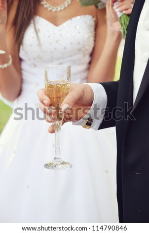 Groom holding a glass of champagne and the element of a bride's dress - stock photo