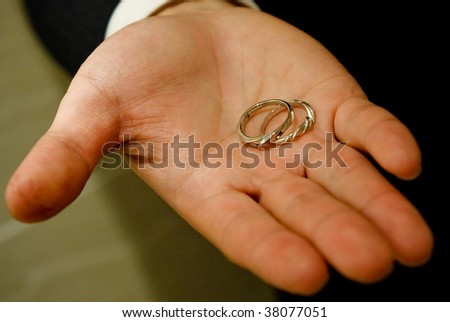 Groom holding the wedding rings on his hand
