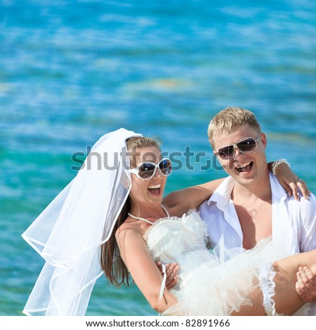 Groom holding up a bride on the beach