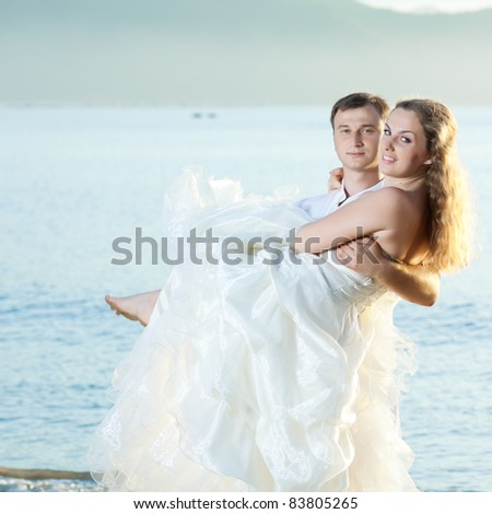 Groom holding up a his bride on the beach - stock photo