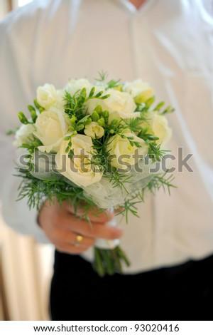 groom holding wedding bouquet in hand - stock photo
