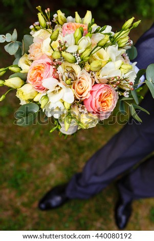 Groom holding wedding bouquet with rings before ceremony outdoors, Close-up picture - stock photo