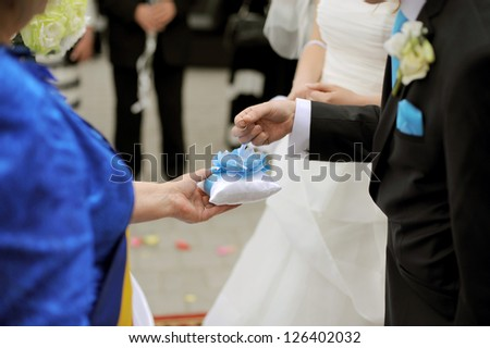 groom holding wedding ring during ceremony