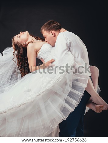 groom holds his bride in his arms and kisses her breasts. Bride and groom portrait in studio. Studio portrait of young elegant enamored just married bride and groom and embracing on black background
