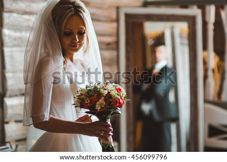 Groom hugs a pretty bride standing in the old-fashioned room. Groom holds bride's waist tender posing between old wooden mirrors