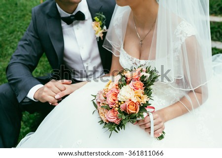 groom in suit with boutonniere and bow-tie holding a bride hand with with veil and wedding bouquet on wedding ceremony - stock photo