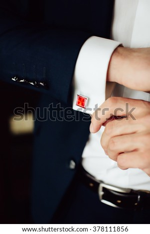 groom in the morning on the wedding day buttoning cuffs his hands on his suit. Close up - stock photo