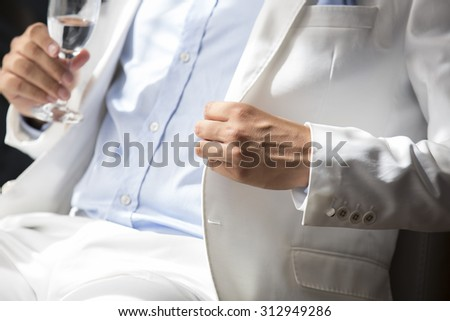 Groom in the white suit detail - stock photo