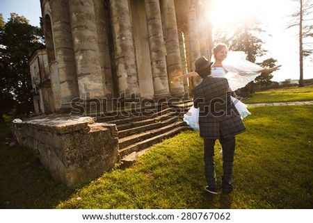 groom is holding his beautiful bride on the background grass and architecture - stock photo