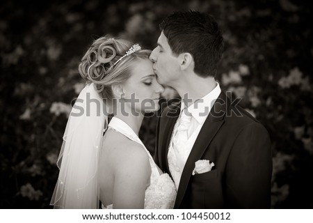 groom is kissing his bride very tender on forehead. black and white photo. - stock photo