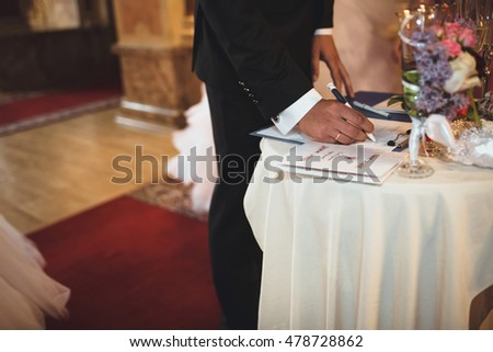 Groom is signing an official document of the marriage
