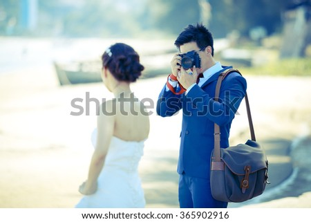 Groom is taking a photo of his bride on the beach. - (Selective focus / Mood and tone) - stock photo