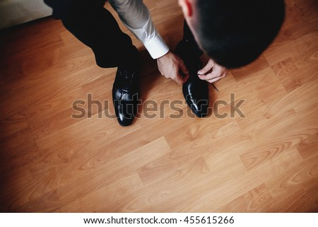 Groom is tying shoelaces on the wedding shoes