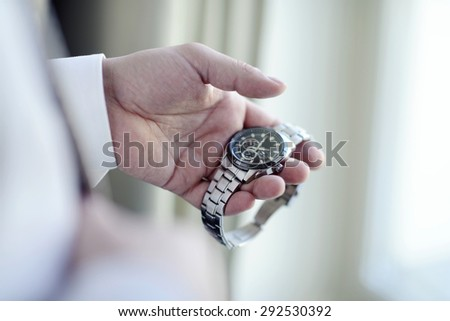 Groom is wearing a wrist watch indoors. Male portrait of handsome guy. Beautiful model boy in colorful wedding clothes. Man is posing - stock photo