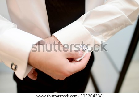 Groom is wearing cufflinks indoors. Male portrait of handsome guy. Beautiful model boy in colorful wedding clothes. Man is posing - stock photo