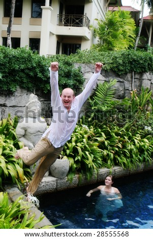 Groom jumps into the water during a trash the dress photo shoot.