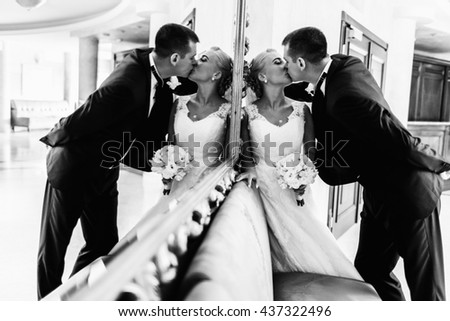 Groom kisses a bride leaning her to a wall behind a big mirror