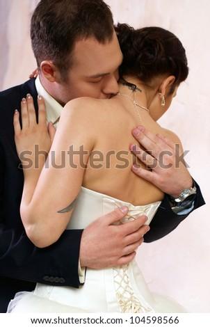groom kisses bride in stylish empty room - stock photo