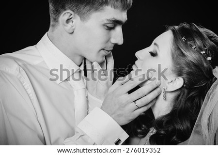 Groom kissing bride on wedding. Black background