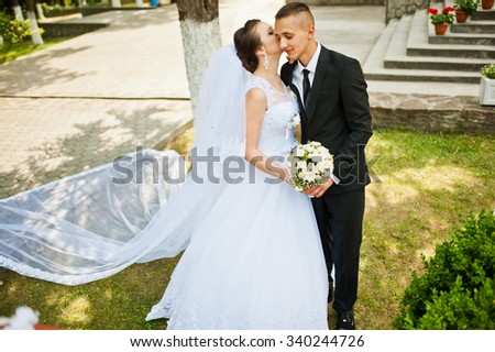 groom kissing bride with awesome long veil