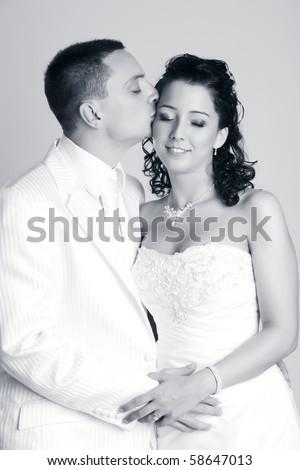 Groom kissing the Bride in studio - stock photo
